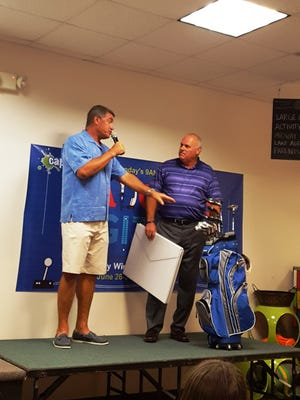 Pete Kugler gives Pastor Curt Ayers a giant thank you card signed by many of the members of Capri Christian Church, along with a new set of golf clubs purchased with donations from the church membership.