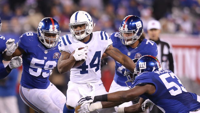 Indianapolis Colts Ahmad Bradshaw looks for a hole in the third quarter against a trio of Giants. Indianapolis traveled to New York for Monday Night Football on November 3, 2014.