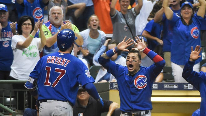 Cubs third baseman Kris Bryant is greeted by Javier Baez after Bryant hit a two-run homer in the tenth inning at Miller Park.