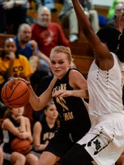 Delone Catholic's Katie Laughman, left, drives to the hoop against Neumann-Goretti's Alicia Kebbe during Friday's PIAA Class AA tournament opener at Archbishop Ryan. Delone Catholic fell to Neumann-Goretti, 49-24.