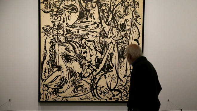 """A patron looks at painting displayed in the exhibit """"Jackson Pollock: Blind Spots"""" at the Dallas Museum of Art on Nov. 18 in Dallas. The largest survey ever assembled of Jackson Pollock's lesser-known """"black paintings"""" is going on display including more than 70 works,  with paintings, sculptures, drawings and prints. The show, running through March 20, includes many works that haven't been exhibited in more than 50 years."""