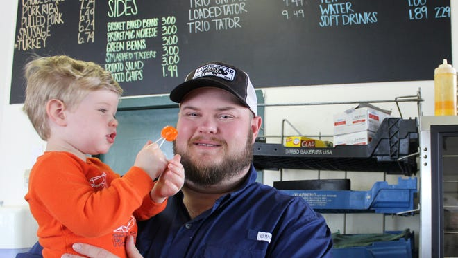 Ellis Proctor, almost 3, enjoys a sucker while his dad, Matt, talks about Stillwater Barbeque being listed among the Top 50 joints in the state by Texas Monthly magazine. The 2017 listing, the first in four years, was announced online Monday.