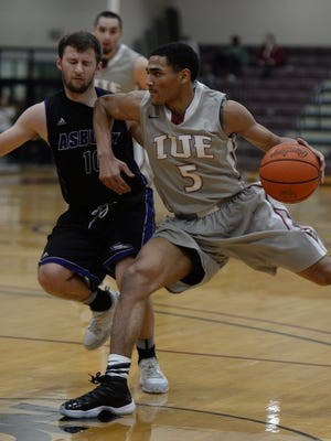 Indiana University East's Jacoby Claypool moves the ball against Asbury's Jordan Gilbert during the KIAC basketball tournament Wednesday, Feb. 24, 2016, at Earlham College in Richmond.