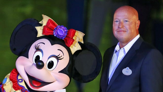 In this Sept. 11, 2015, file photo, Chairman of Walt Disney Parks and Resorts Bob Chapek poses with Minnie Mouse during a ceremony at the Hong Kong Disneyland, as they celebrate the park's 10th anniversary. The Walt Disney Co. has named Chapek CEO, replacing Bob Iger, effective immediately, the company announced Tuesday.