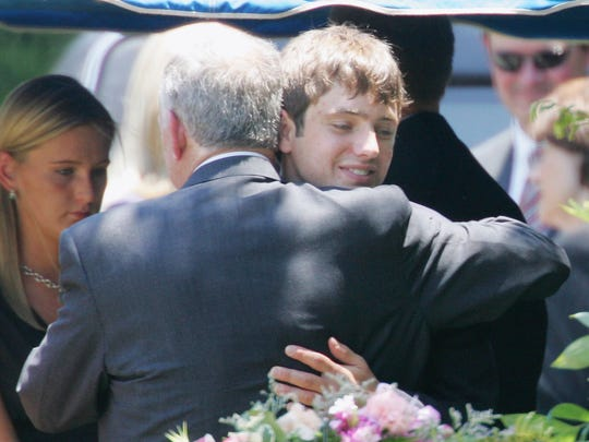 John Ramsey hugs his son, Burke, facing camera, at the graves of his wife, Patsy, and daughter, JonBenet, during services for his wife June 29, 2006, at the St. James Episcopal Cemetery in Marietta, Ga.