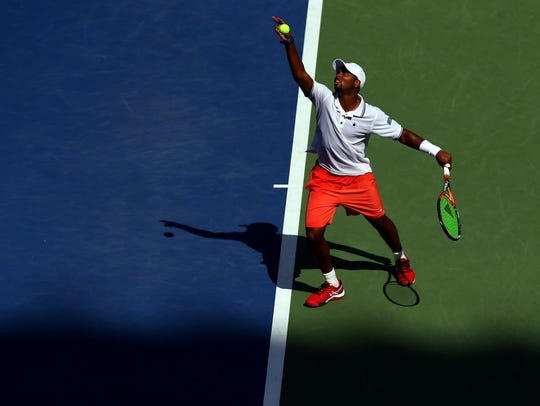 Donald Young of the United States serves to Stan Wawrinka