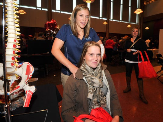 Megan Korntved, bottom, of Marshfield, receives a massage from chiropractic Casey Long during Thursday night's Taste of Home Cooking School at The Grand in downtown Wausau.