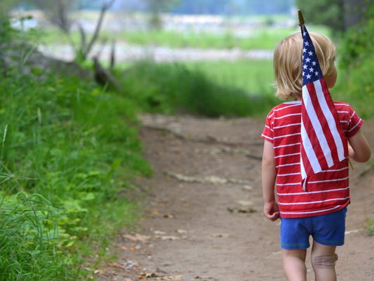 Young boy holding American Flag