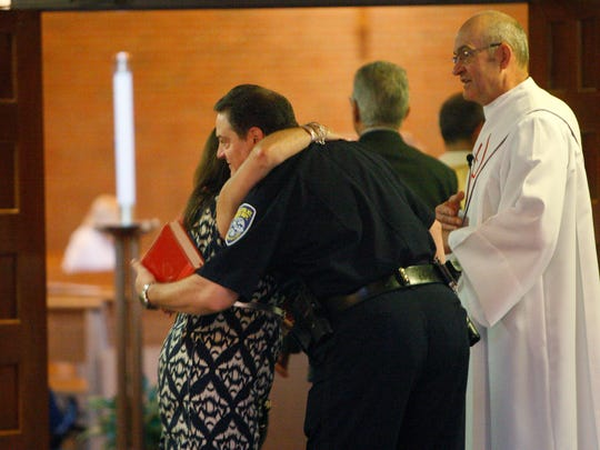 County Legislator Karla Boyce of Mendon gives Commander Joseph Morabito a hug while Deacon Wil Johnson waits to chat with him. Johnson also a captain with Rochester police.