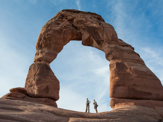 636035919461157229-Hikers-stand-under-Delicate-Arch-2-VisitUtah.jpg