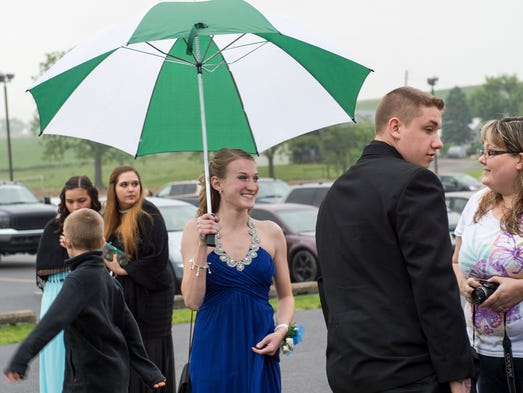 Autimn Leidig holds an umbrella as she waits to go