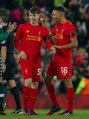 Ben Woodburn (CL) celebrates Liverpool's 2-0 victory with Trent Alexander-Arnold.