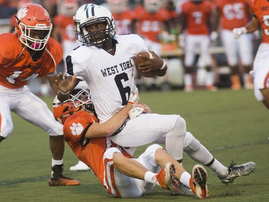 West York's Anton D. Johnson II, top, is tackled by