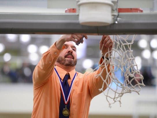 William Penn head coach Troy Sowers cuts the net after