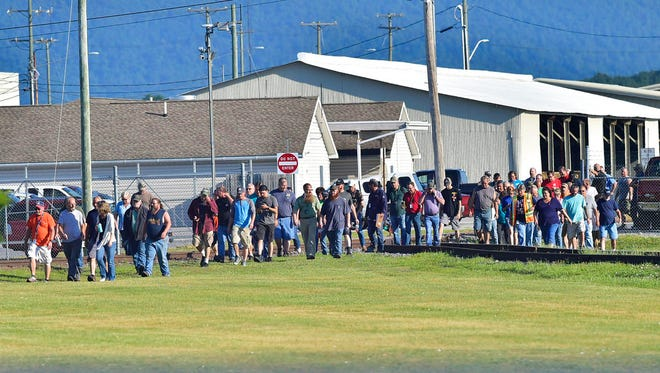 Employees evacuate the area following an incident Thursday, July 19, 2018, at Letterkenny Army Depot in Chambersburg, Pa.. A small explosion Thursday in a vehicle shop at the Army depot injured at least four workers, three of them seriously, officials said. (Markell DeLoatch/Public Opinion via AP)