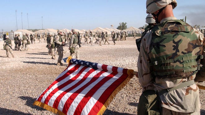 A U.S soldier rolls up an American flag at the end of a ceremony at Camp Striker in Baghdad in 2004.
