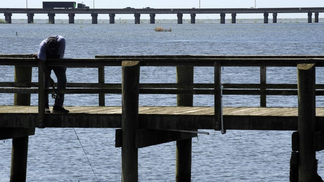 A man fishes on a pier as traffic on Interstate 10 crosses Mobile Bay at Spanish Fort, Ala. Officials in Baldwin County took a decisive stand against a plan to use tolls to pay for a replacement bridge and roadway, prompting Alabama Gov. Kay Ivey to say the project is now dead.