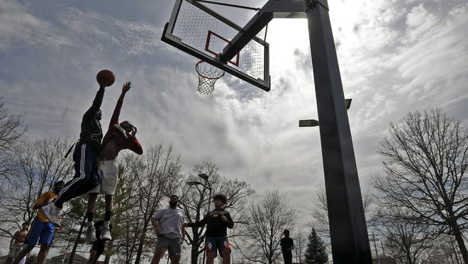 Youths play basketball on the courts at Livingston Park located next to Children's Hospital in Columbus back in March.