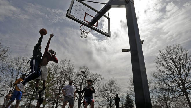 Youths play basketball on the courts at Livingston Park located next to Nationwide Children's Hospital on March 26.