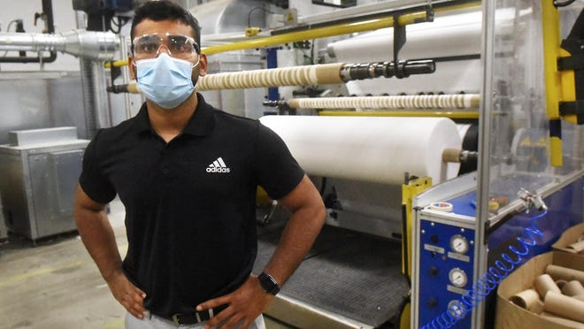 Sumit Phalakm, a Lydall Performance Materials development engineer, stands in front of a filtration performance layer machine, which is designed to create material for N95 masks and respirators at the Rochester facility.