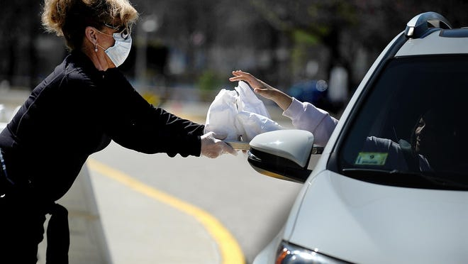Kathy Hopkins brings meals to a car at the Cameron Middle School in March.