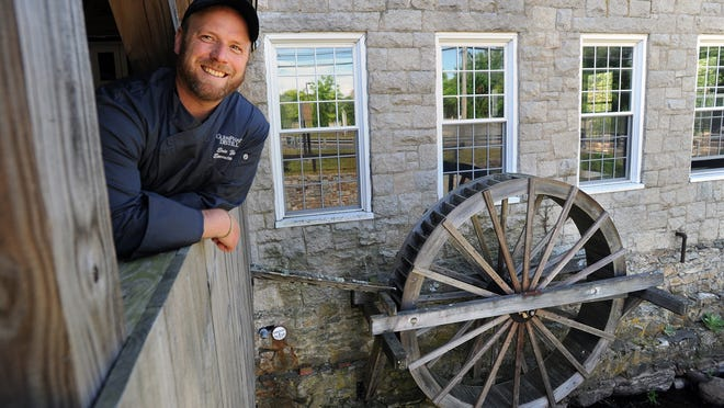 GlenPharmer Distillery Executive Chef Eric Zediker poses by the mill wheel in the historic building on West Central Street in Franklin that was previously the Incontro Restaurant.