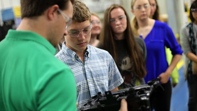 Connor Ervin and Griffin Dodd, left, and other Central Magnet students look at a rocker (head) cover for a Nissan engine during tour of MAHLE Wednesday, Oct. 1, 2014.