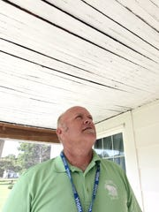 Scott Smith of First State Community Action Agency checks a home in Lincoln where lead paint was used. Lead paint was banned in the United States in 1978, but thousands of homes built before that date still are coated with it inside and out.
