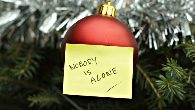 """An ornament dangling from a Christmas tree wears a Post-it note that reads """"Nobody is alone."""""""