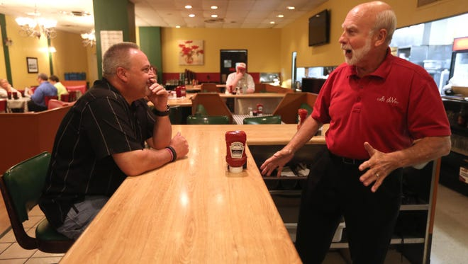 Keith Strunk, a regular costumer, talks with Steve Creech, during the lunch rush at Cafe deVine, on Wednesday afternoon. The last day for the restaurant, currently in the 309 Vine building, will be Friday, Sept.18. Creech owns the restaurant with his wife, Faye.