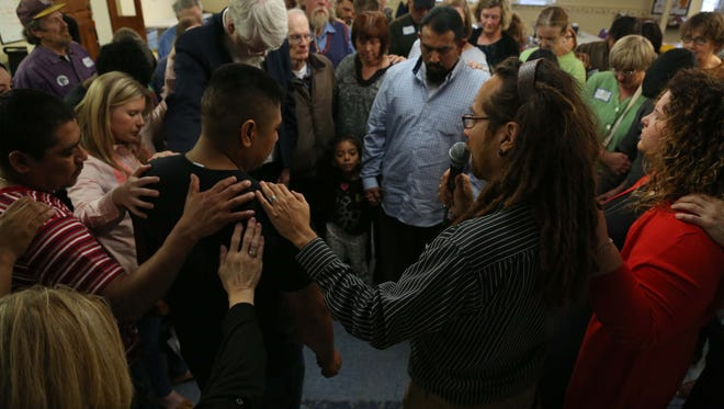 During a vigil for local immigration leader Constantino Morales Roque, who was killed in Mexico recently after being deported last fall, people place their hands on the shoulder of his brother Leonardo during a prayer on Sunday, April 12, 2015, at Trinity United Methodist in Des Moines.
