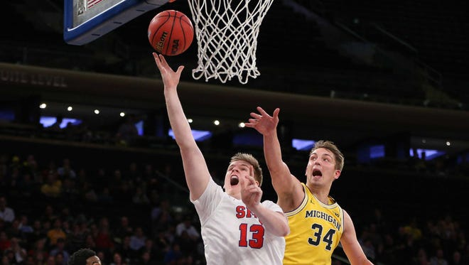 SMU forward Harry Froling (13) lays the ball up as Michigan forward Mark Donnal (34) defends during the championship game of the 2016 2K Classic at Madison Square Garden.