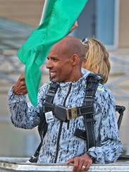 Meb Keflezighi waves a green flag to start the OneAmerica