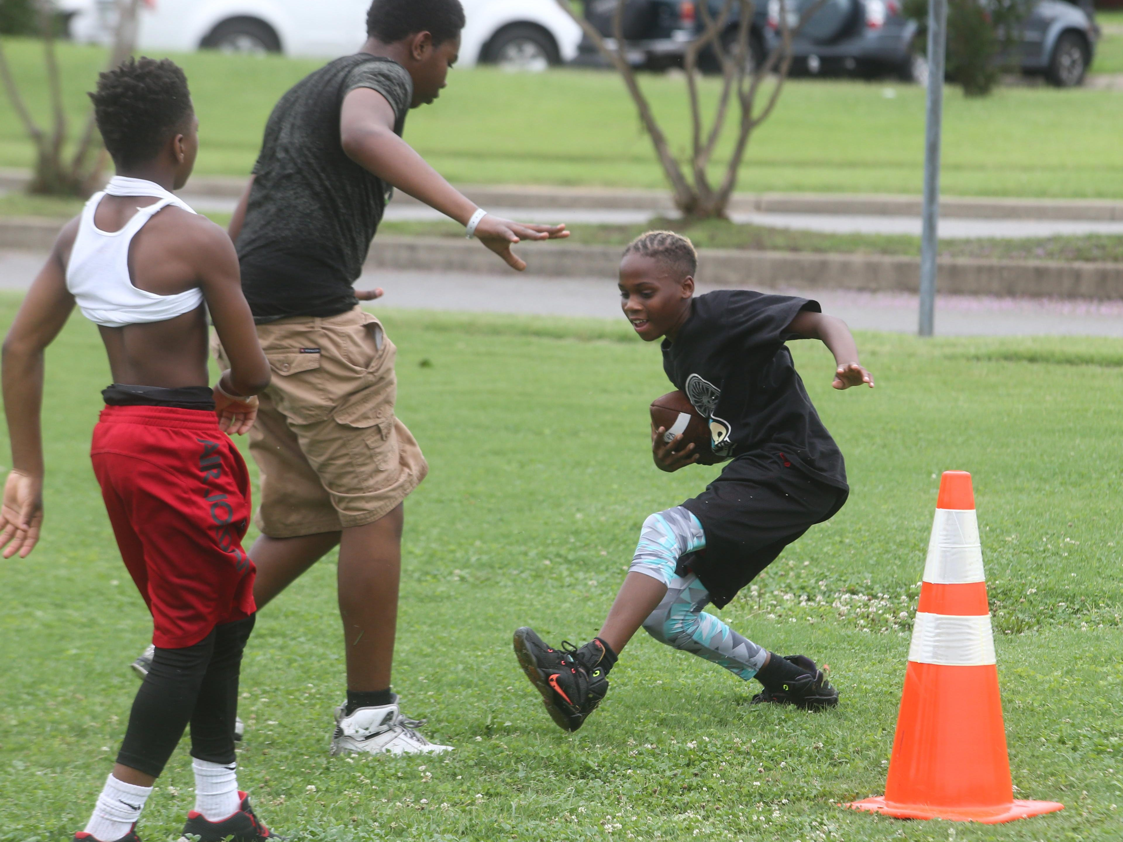 Whitworth Buchanan student Marshawn Scales, 13, tries to miss a defender while going for the end zone.