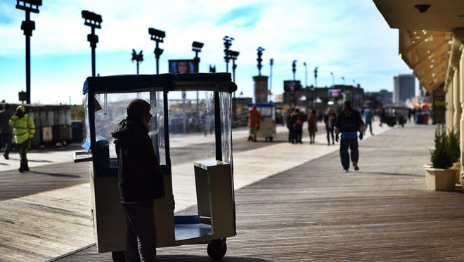 """A man waits for passengers to ride his """"push taxi"""" along the boardwalk in Atlantic City, New Jersey, on November 8, 2014."""