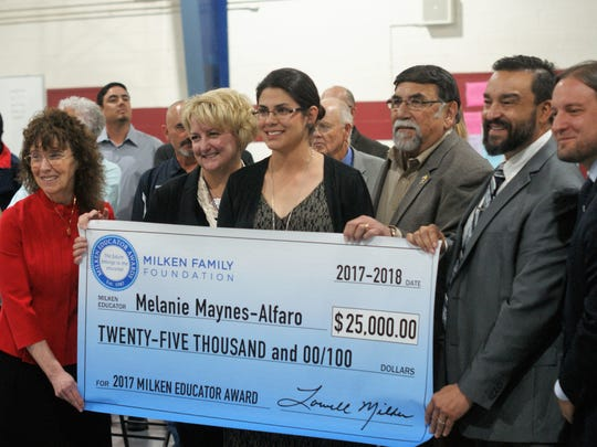 Melanie Alfaro, center, was surprised by the award, which comes with a $25,000 unrestricted cash prize. At left is Dr. Jane Foley of the Milken Educator Awards. On the right are DPS Superintendent Arsenio Romero and NM PED Secretary-designate Christopher Ruszkowski.