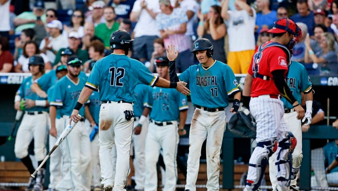Jun 28, 2016: Coastal Carolina Chanticleers catcher David Parrett (12) and center fielder Billy Cooke (17) celebrate after scoring runs during the second inning against the Arizona Wildcats in game two of the College World Series championship series at TD Ameritrade Park.