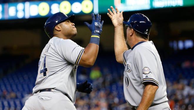 Jesus Aguilar (24) celebrates his home run with third base coach Ed Sedar.