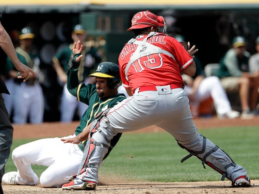 Oakland Athletics' Marcus Semien, left, scores past Los Angeles Angels catcher Juan Graterol (13) on single by Chad Pinder during the fifth inning of a baseball game Wednesday, Sept. 6, 2017, in Oakland, Calif. (AP Photo/Marcio Jose Sanchez)