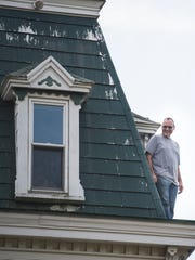 Paul Brubaker stands on the roof of the home as Wolfe House & Building Movers moved the late 1700s home a quarter mile in Millcreek Township on Wednesday, Aug. 31, 2016.