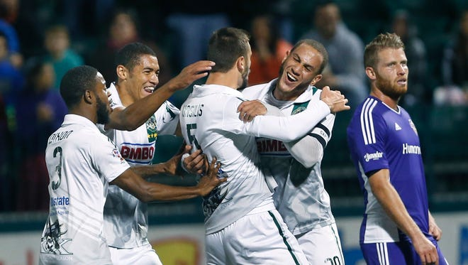 Rhinos captain Tony Walls, right, and defender Vassilis Apostolopoulos celebrate Apostolopoulos' goal against Louisville City in the first half of a playoff match last season.