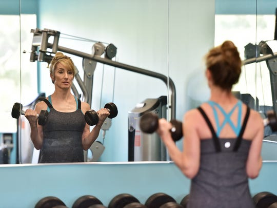 Kaye uses dumbbells within her workout to increase arm strength.
