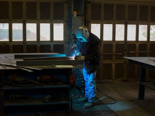 Mark Stevens, 50, welds a metal pallet for a local business on Monday, November 21, 2017 at Stevens Custom Welding in Port Huron.