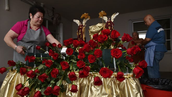 """Fred and Bertha Tanaka of Nichol's Boutique and their staff decorated the karosa for the Santa Marian Kamalen procession early Tuesday morning. The couple have been quietly donating flowers and services for the celebration of the feast of the Immaculate Conception for 30 years, said their daughter Nichol Tanaka Napoleon. """"(They) are very private people and don't seek recognition,"""" Napoleon said. """"They began this tradition a year after their shop, Nichol's Boutique, began selling fresh flowers in 1984 and have never missed a year since."""" The couple work early in the morning so the karosa is decorated before a crowd forms, Bertha Tanaka said. """"I usually start in the front and my husband starts in the back, and we meet in the middle and it all comes together, like a puzzle,"""" she smiled. """"We are low key people,"""" Fred Tanaka said, of not wanting recognition. """"We make the best of the profession we are in. It's all about sharing,"""" he said. Their faith and love of the church guides their work, Bertha Tanaka said. """"When I come in in the morning, I think, 'where do I start.' I always ask (Santa Marian Kamalen) to guide us and we always get through it."""""""