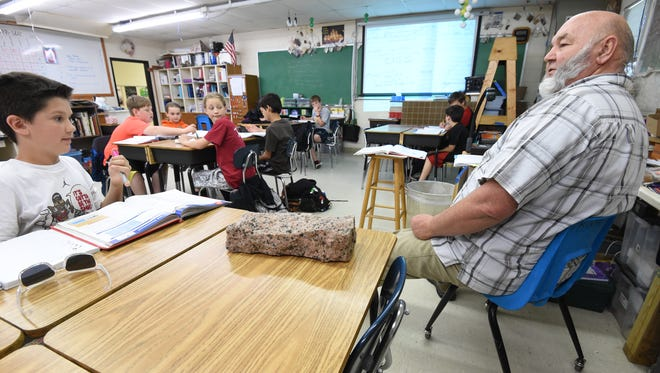 Norfork Elementary School Science teacher Wade Geery, right, asks fifth-grader Andrew Knierim on Tuesday what shape the path the orbits of planets resemble. Norfork schools recently received money for being in the top 5 percent of schools based on student performance.