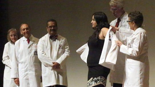 Nicole Loper, of El Paso, puts on her white coat with