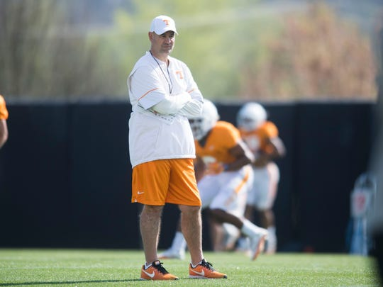Tennessee head coach Jeremy Pruitt runs on the field with players during a Vols football practice at University of Tennessee Tuesday, April 3, 2018.