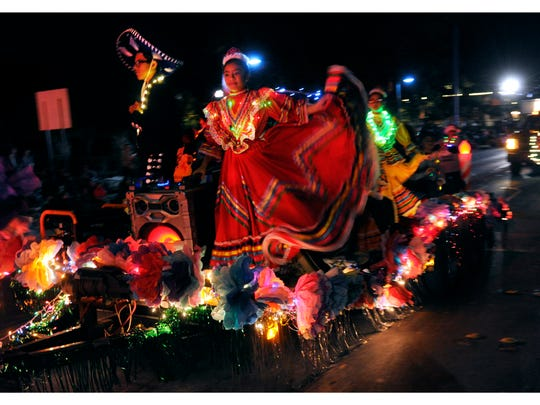 Ballet de Folklorico dancers perform on a float as it proceeds down North First Street during the 2017 City Sidewalks Christmas Lights Parade.