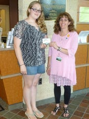 Amber Armstrong (left) receives a $50 gift card from