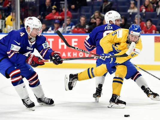 Sweden's Rasmus Dahlin (8) moves the puck around United States' Adam Fox, rear, as United States' Ryan Poehling (4) skates in during the second period of a semifinal game at the world junior hockey championship in Buffalo, N.Y., Thursday, Jan. 4, 2018. (Nathan Denette/The Canadian Press via AP)